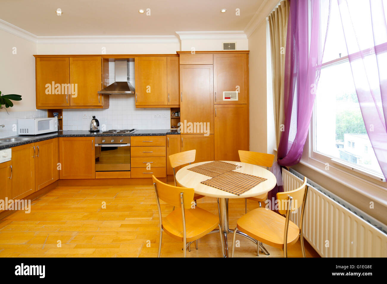 Belsize Lane, Hampstead. View of a kitchen with wood cabinets and dining table. Traditional layout. Stock Photo