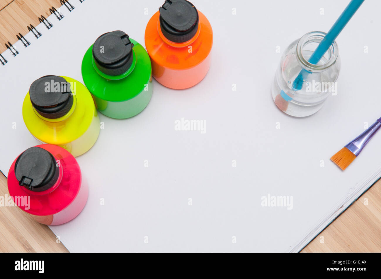 Paint brush in water in front of brightly coloured children\'s paint ...