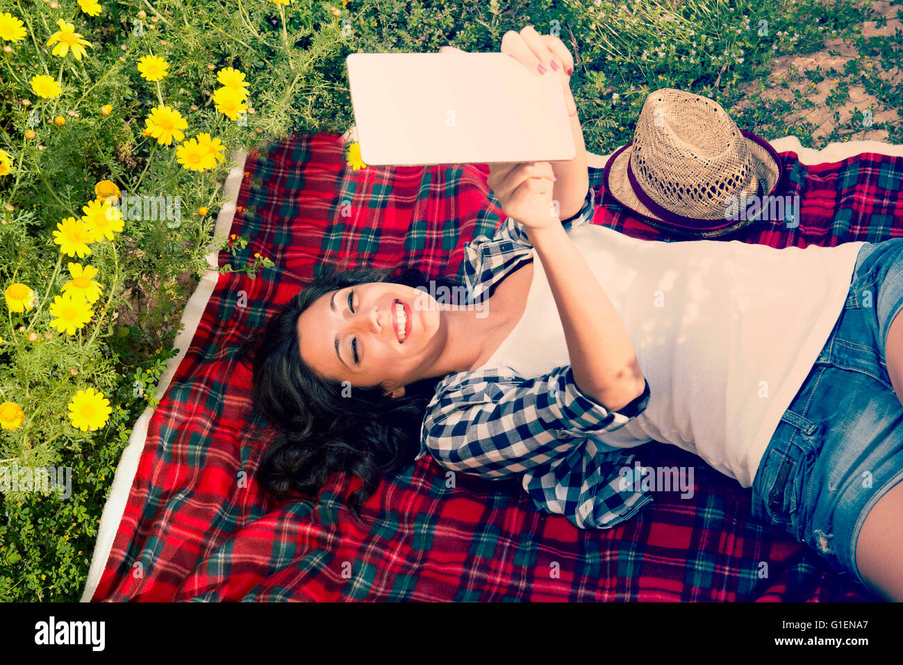 Girl reads a tablet into nature on a blanket - Stock Image