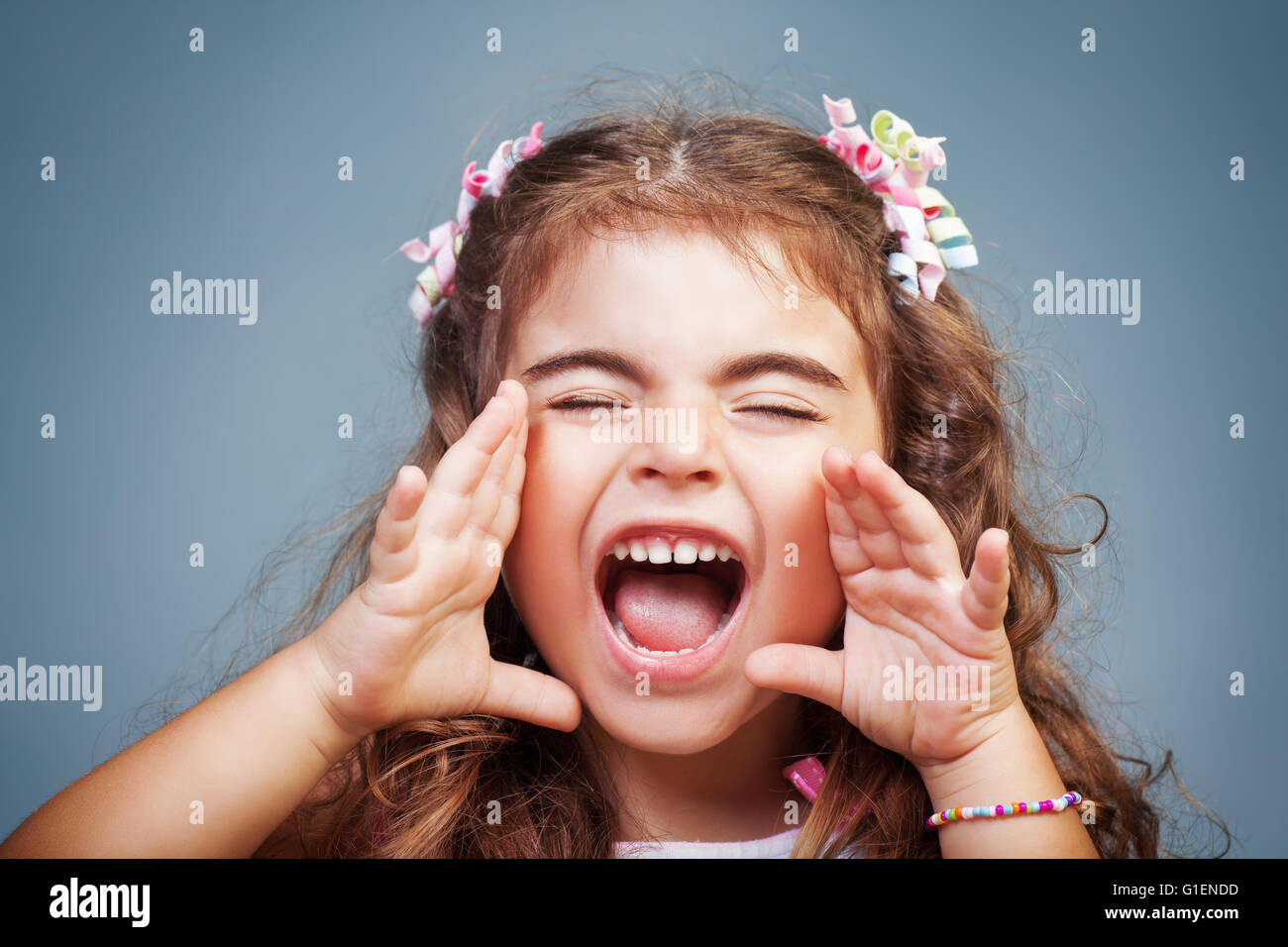Portrait of a cute little baby girl screaming, naughty child yelling, expressing emotions, playful child rave about Stock Photo