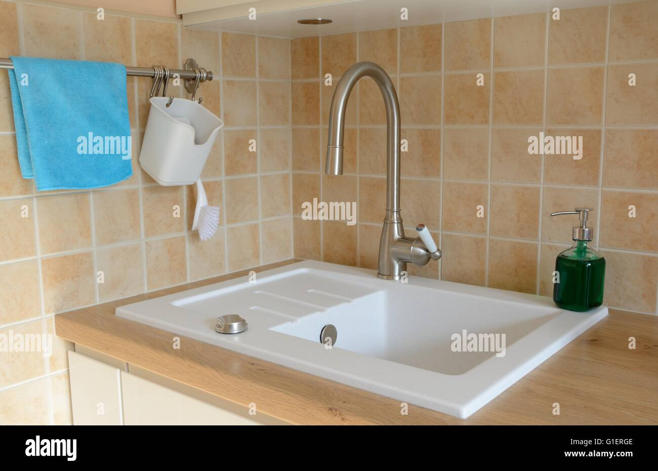 Kitchen sink, tap and other items on brown wooden kitchen counter Stock Photo