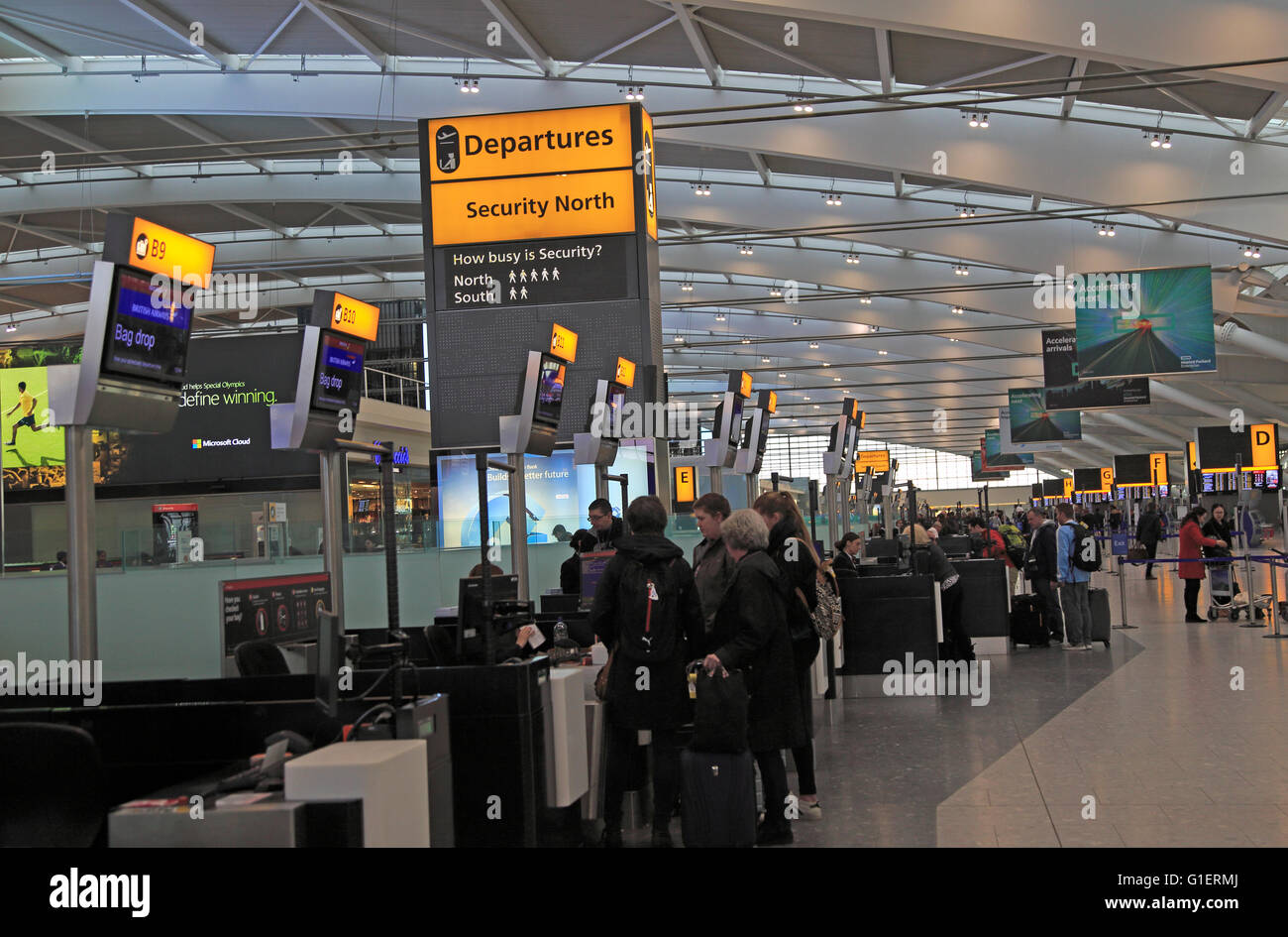 People checking-in at bag drop desk departure area terminal 5 Heathrow airport, London, England, UK - Stock Image