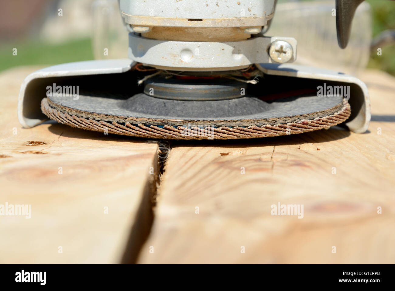 Front part of angle grinder with abrasive disc on planks after work. - Stock Image