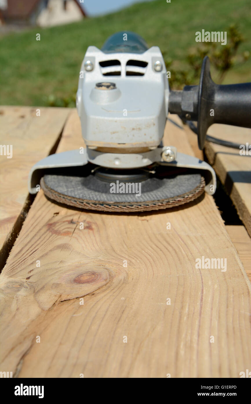 Angle grinder with abrasive disc on plank after work. Blurred background. Focus on wood. Shallow depth of field. - Stock Image