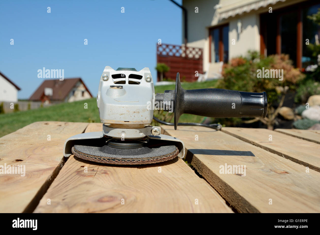 Angle grinder with abrasive disc on planks after work. Stock Photo