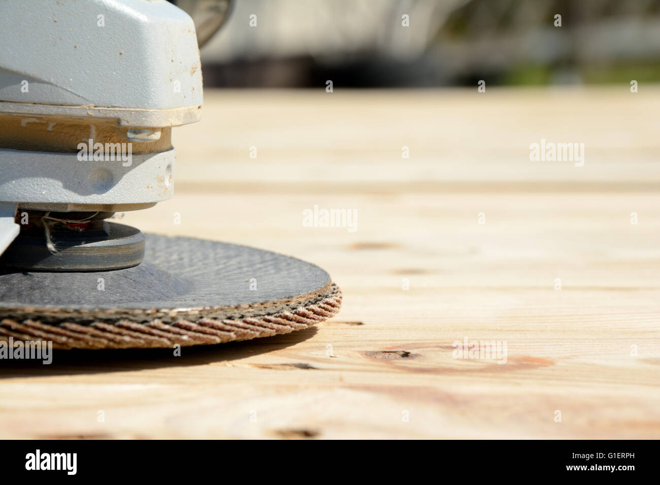 Front part of angle grinder with abrasive disc on planks after work. Shallow depth of field. - Stock Image