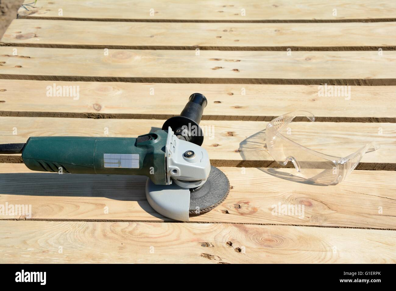 Angle grinder with abrasive disc and protective glasses on planks after work. - Stock Image