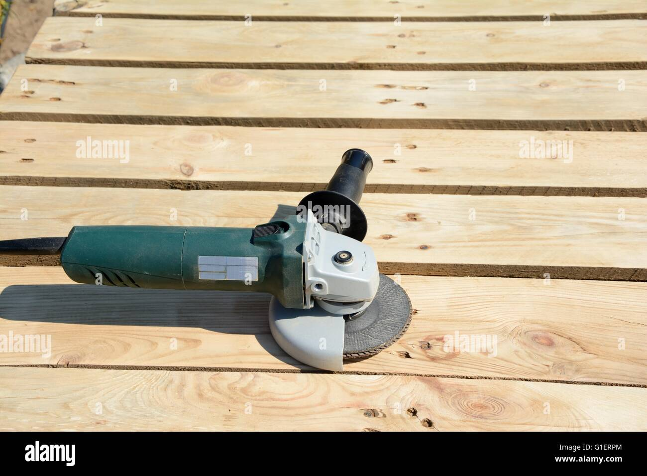 Angle grinder with abrasive disc on planks after work. - Stock Image