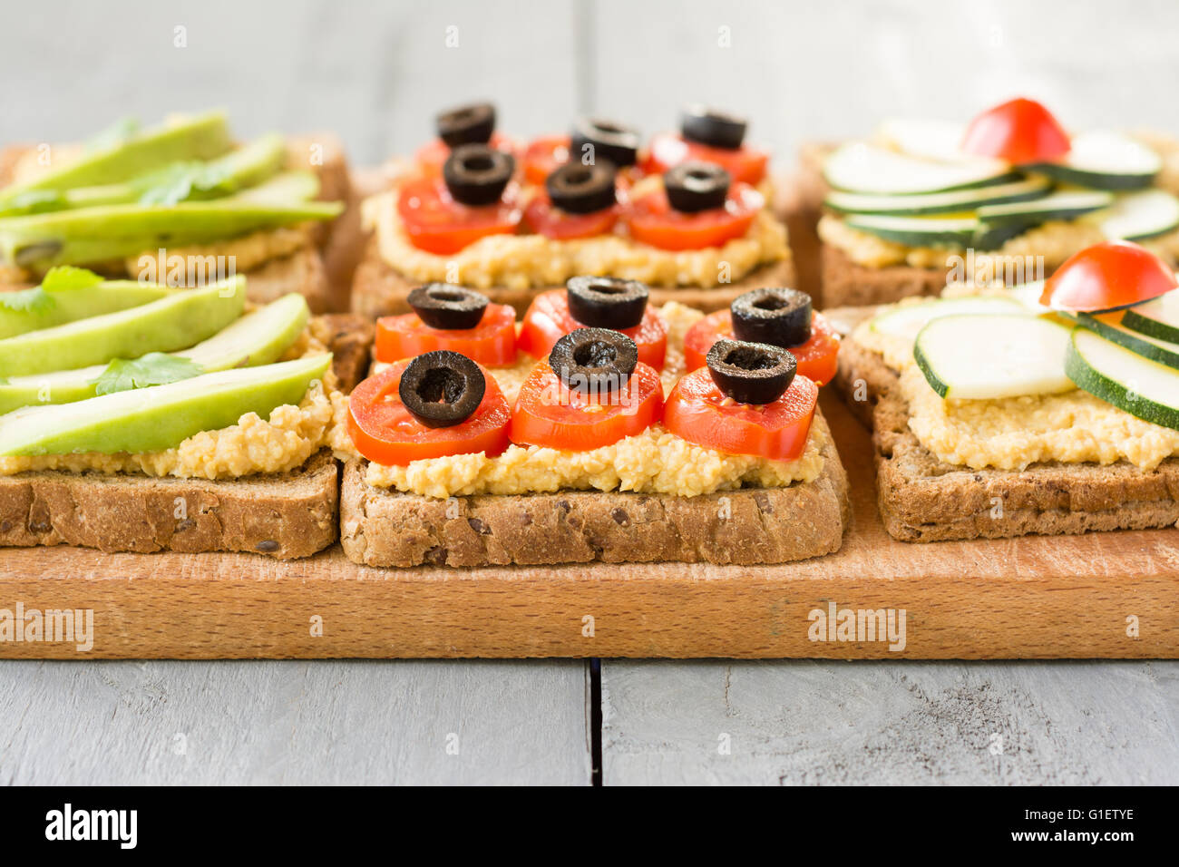 Hummus Toasts with zucchini and a cherry tomato, cherry tomato and black olives and avocado. Stock Photo