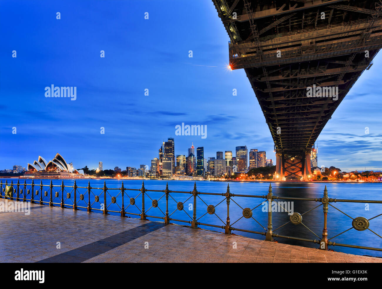 Major Sydney city clandmarks - Harbour Bridge, Circular Quay and CBD skyscrapers at sunset across harbour from Milsons - Stock Image