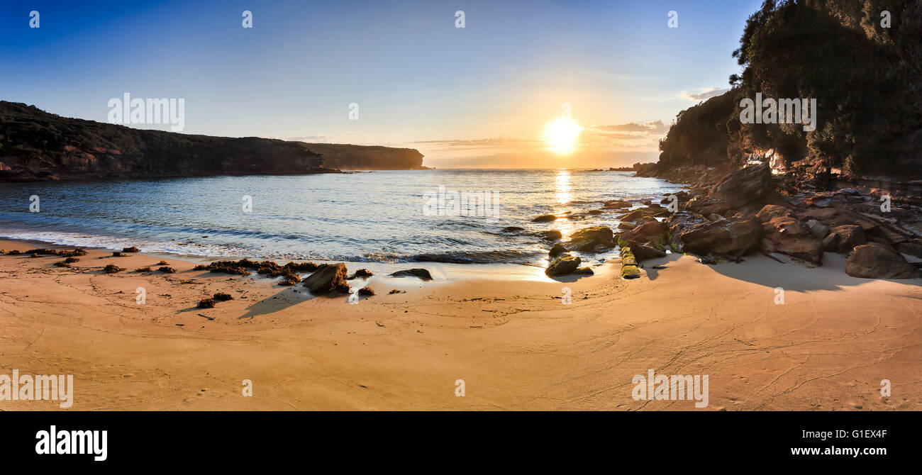 WIde morning panorama of Wattamola beach clean sand and low tide rocks in Royal National park, Australia. Bright - Stock Image