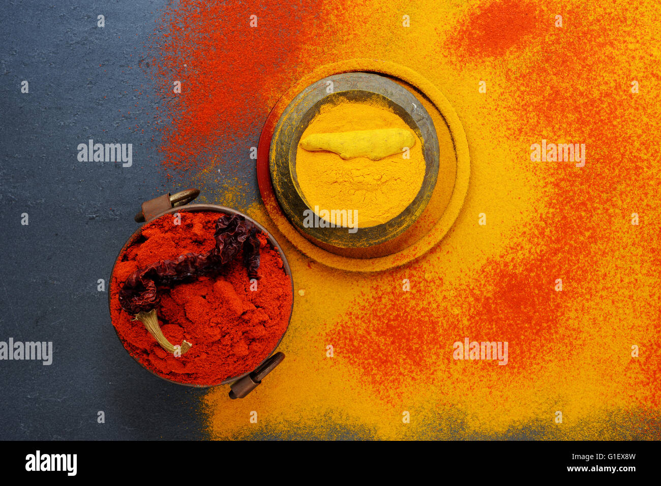 Set of spices pepper and turmeric, in vintage metal cups over yellow turmeric powder. Top view. Food or spicy cooking - Stock Image