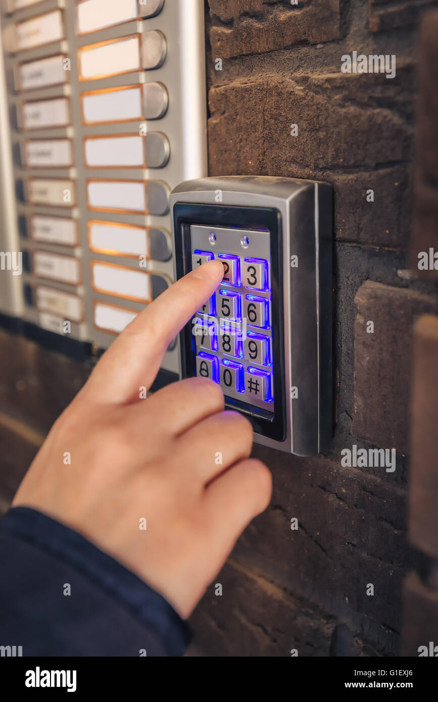 Woman dialing passcode on security keypad to open entrance door of the apartment building. - Stock Image
