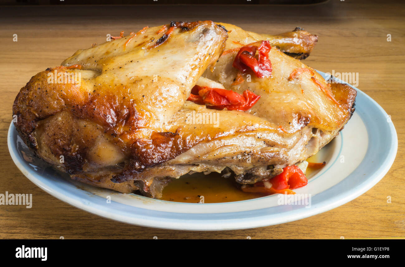 Roasted meat of the hen with red pepper and spice in plate on table Stock Photo