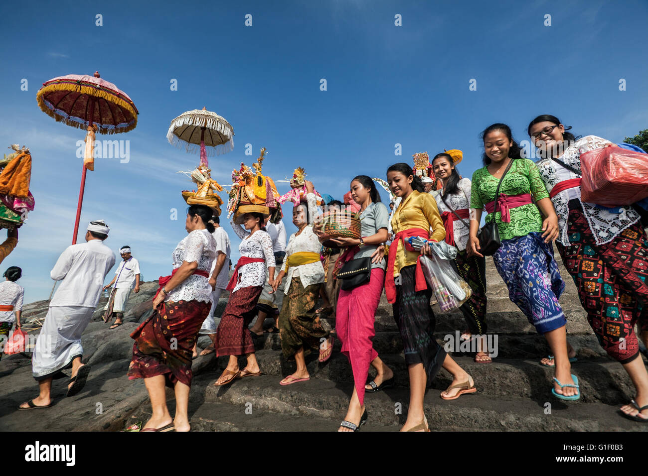 Colourful procession of Indonesian women of the Balinese Hindu faith carrying religious offerings onto a beach in - Stock Image