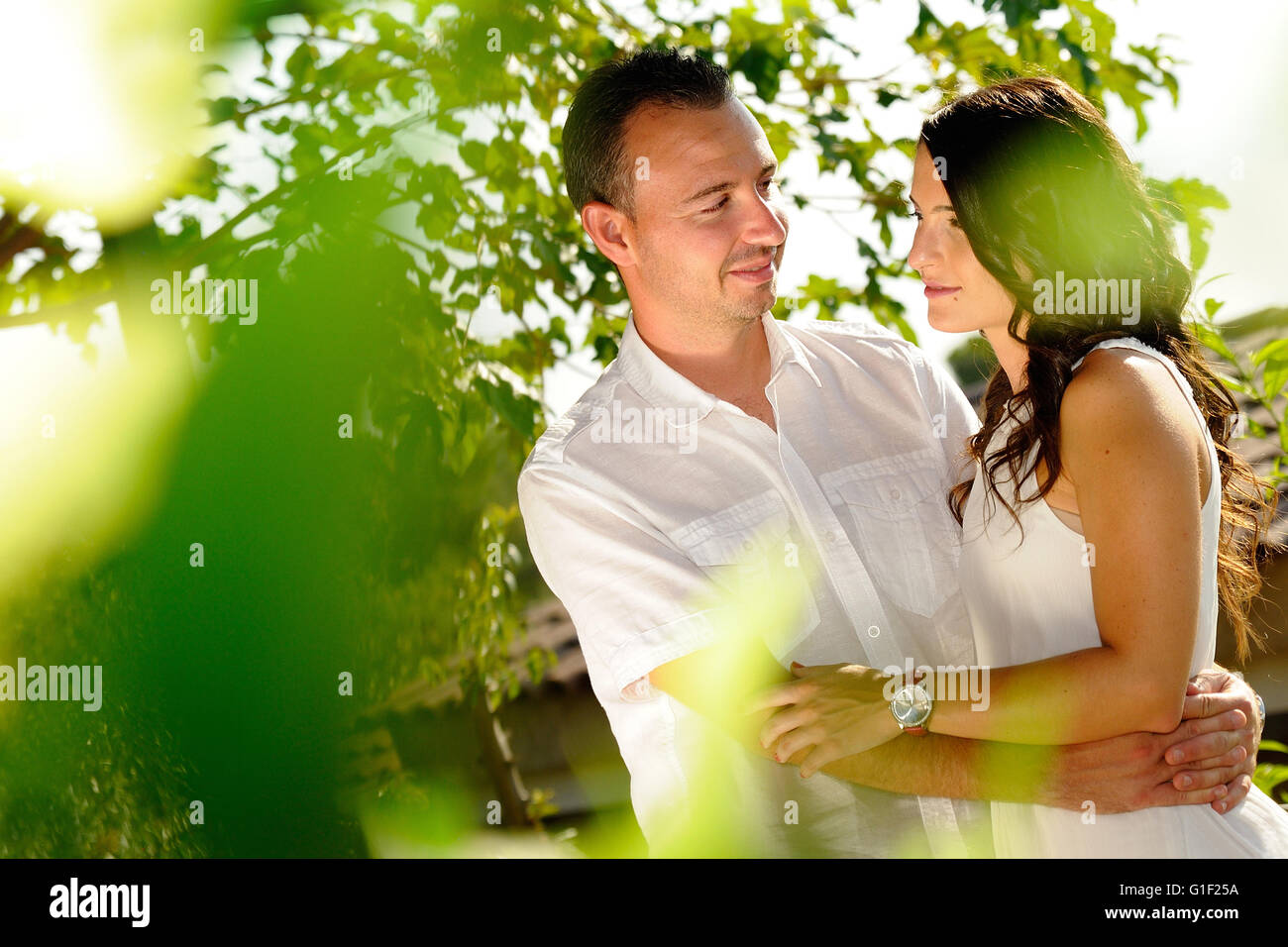 Young couple dressed in white looking accomplices among trees in the field - Stock Image