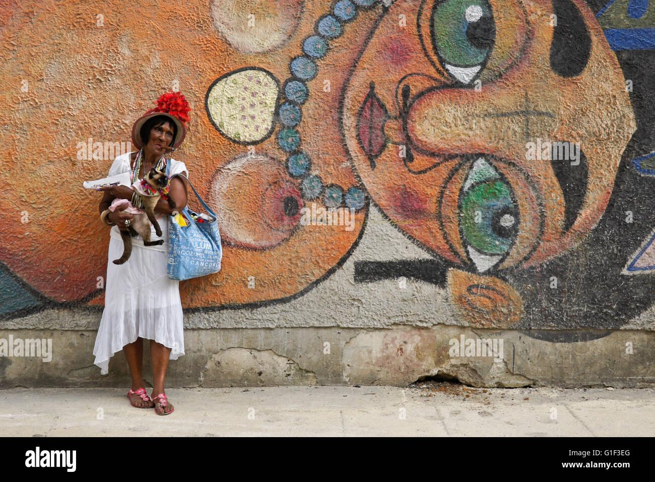 Cigar-smoking woman and her cat in front of street mural, Havana, Cuba - Stock Image