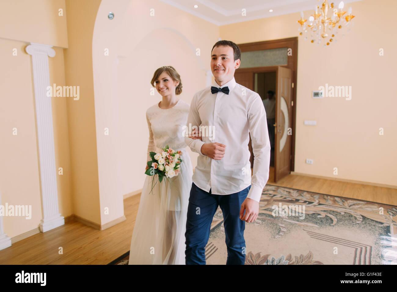 Happy groom and bride walking hand-in-hand at civil registry office ...