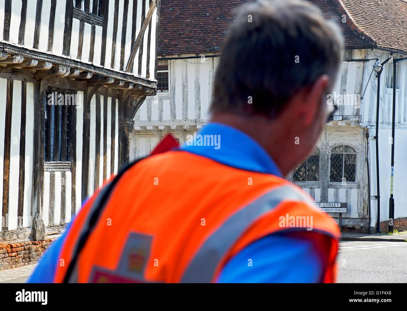 Postman in the medieval village of Lavenham, Suffolk, England UK - Stock Image