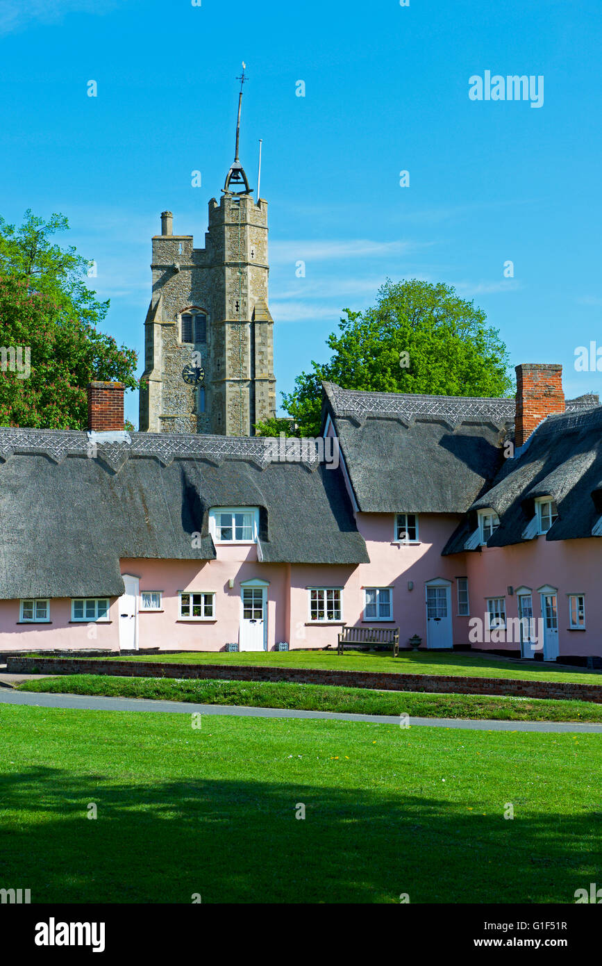 Almshouses - and the tower of St Mary's Church - in the village of Cavendish, Suffolk, England UK - Stock Image