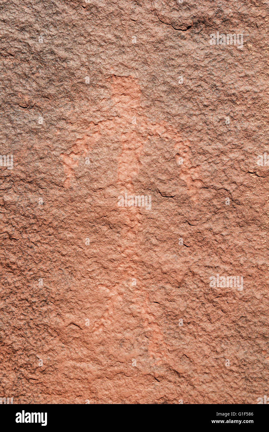 petroglyph of a man on a varnished red sandstone rock - Stock Image