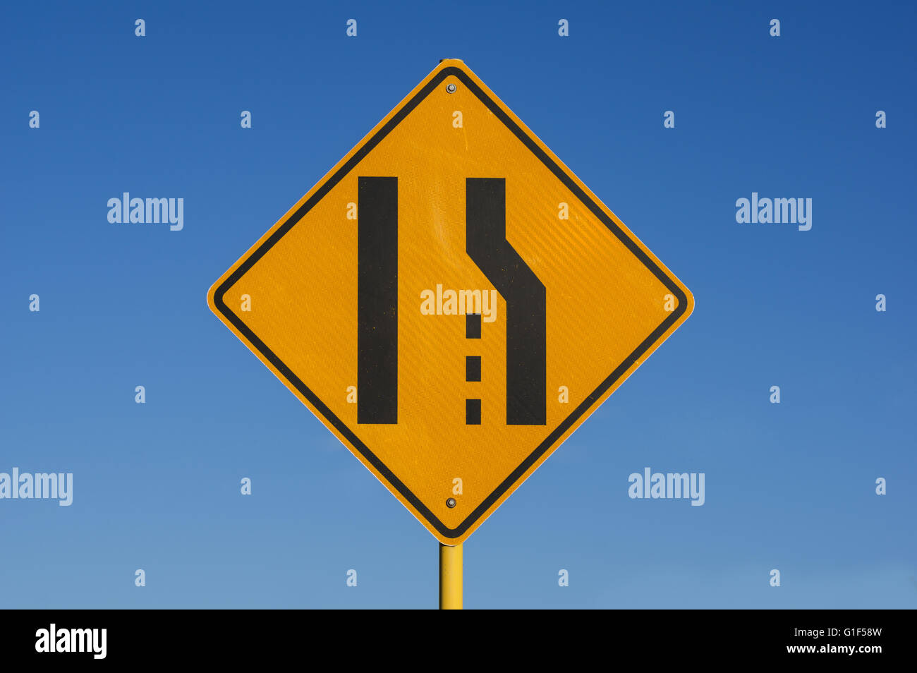 yellow and black right lane ends sign with blue sky background - Stock Image