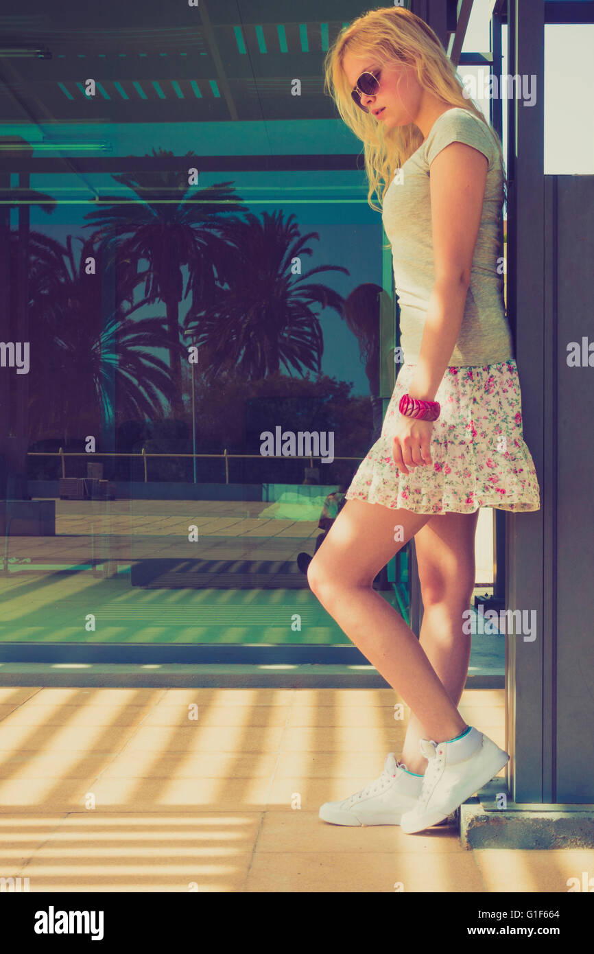 MODEL RELEASED. Young woman wearing mini skirt standing by wall. - Stock Image