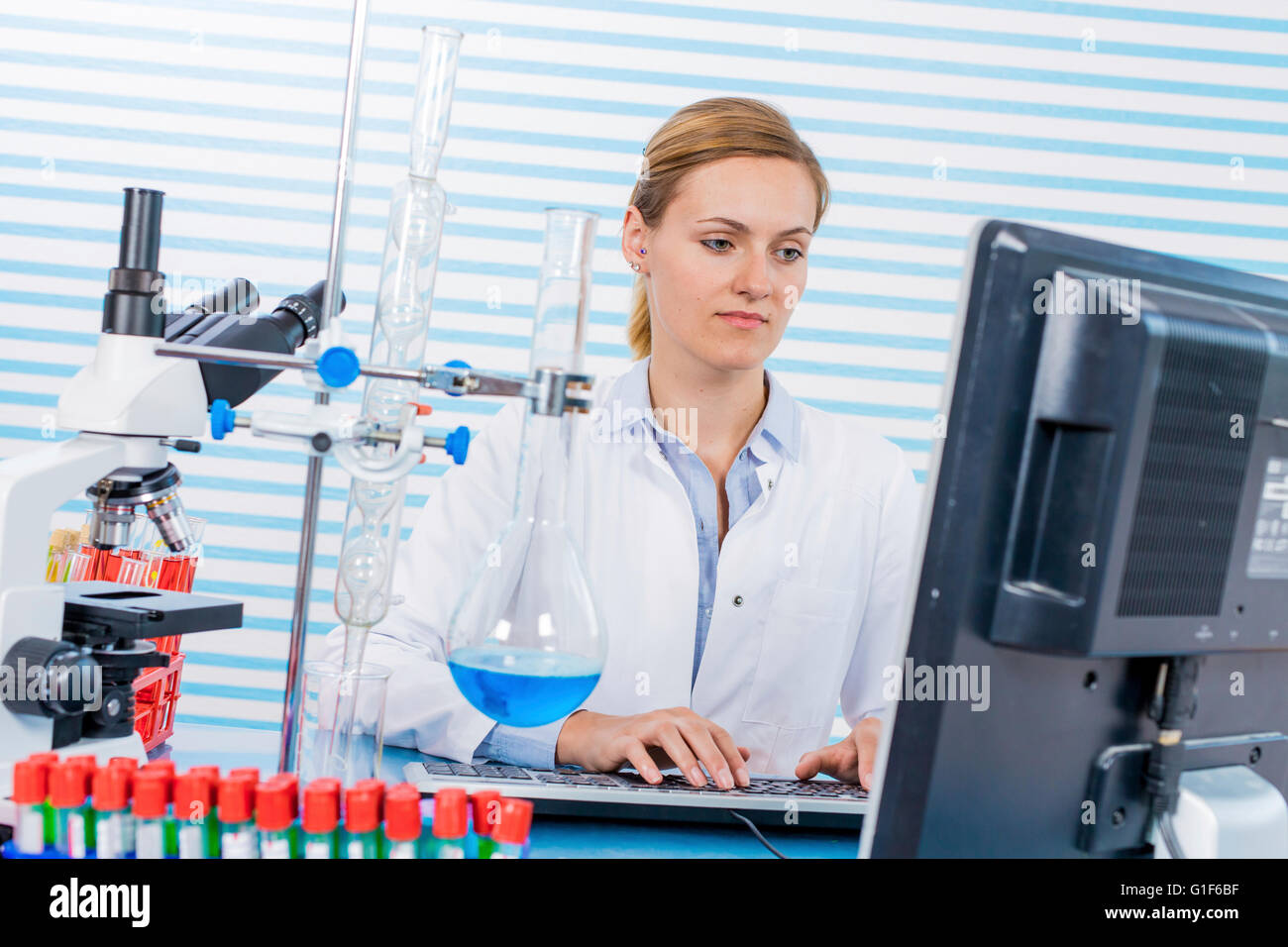 MODEL RELEASED. Female chemist using computer in the laboratory. - Stock Image
