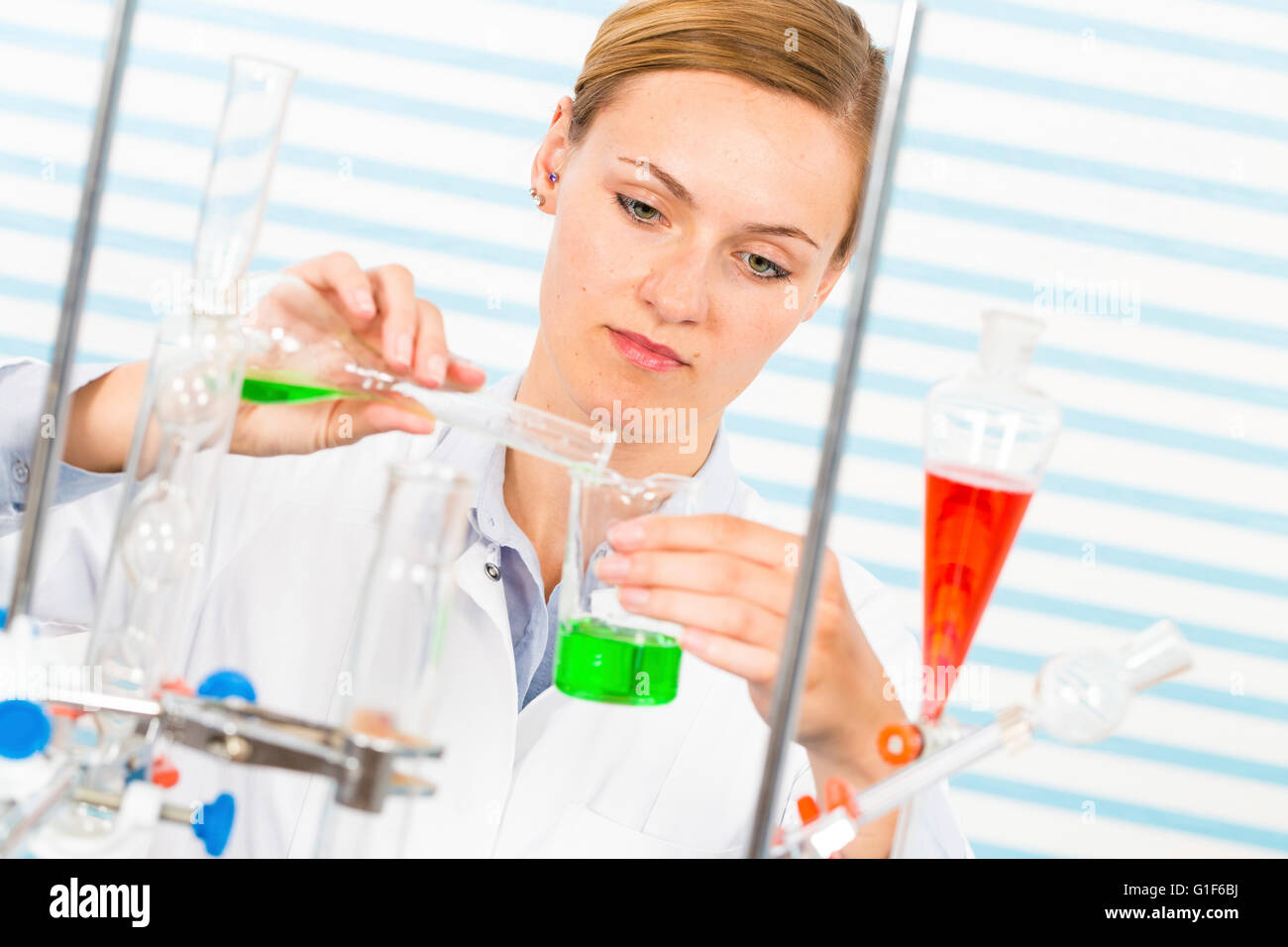 MODEL RELEASED. Female chemist pouring chemicals into glassware in laboratory. Stock Photo