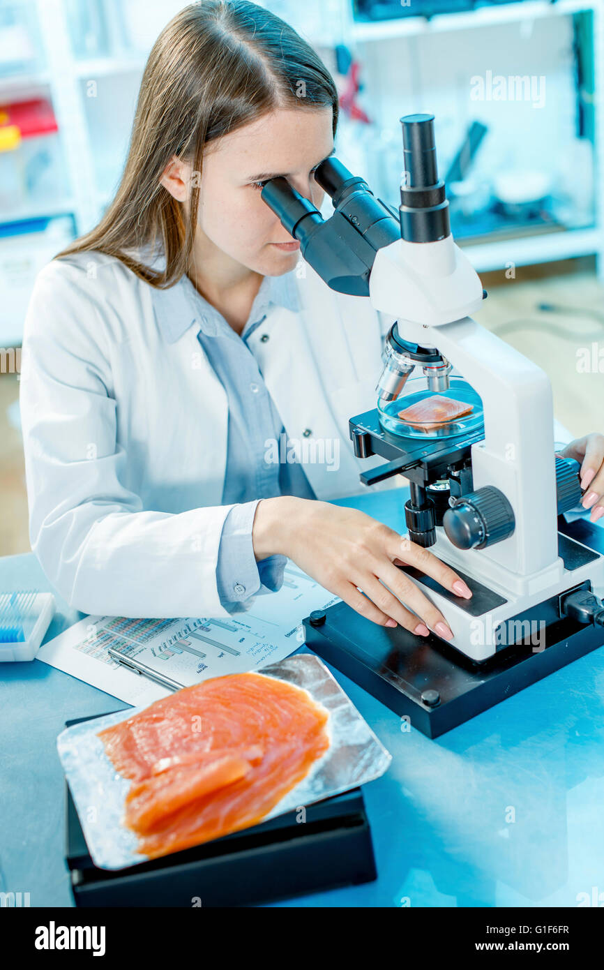 MODEL RELEASED. Female scientist studying salmon under a microscope. - Stock Image