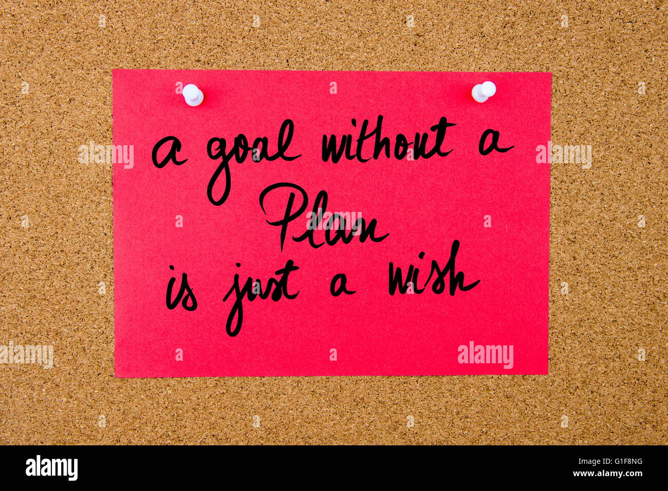 Red paper note with handwritten text A Goal Without A Plan Is Just A Wish pinned on cork board with white thumbtacks Stock Photo