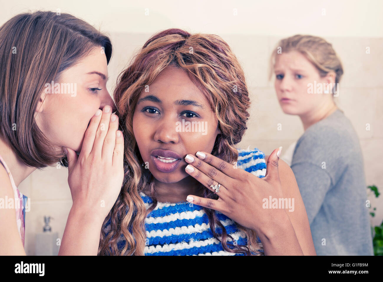 Two young girls share secrets - Stock Image