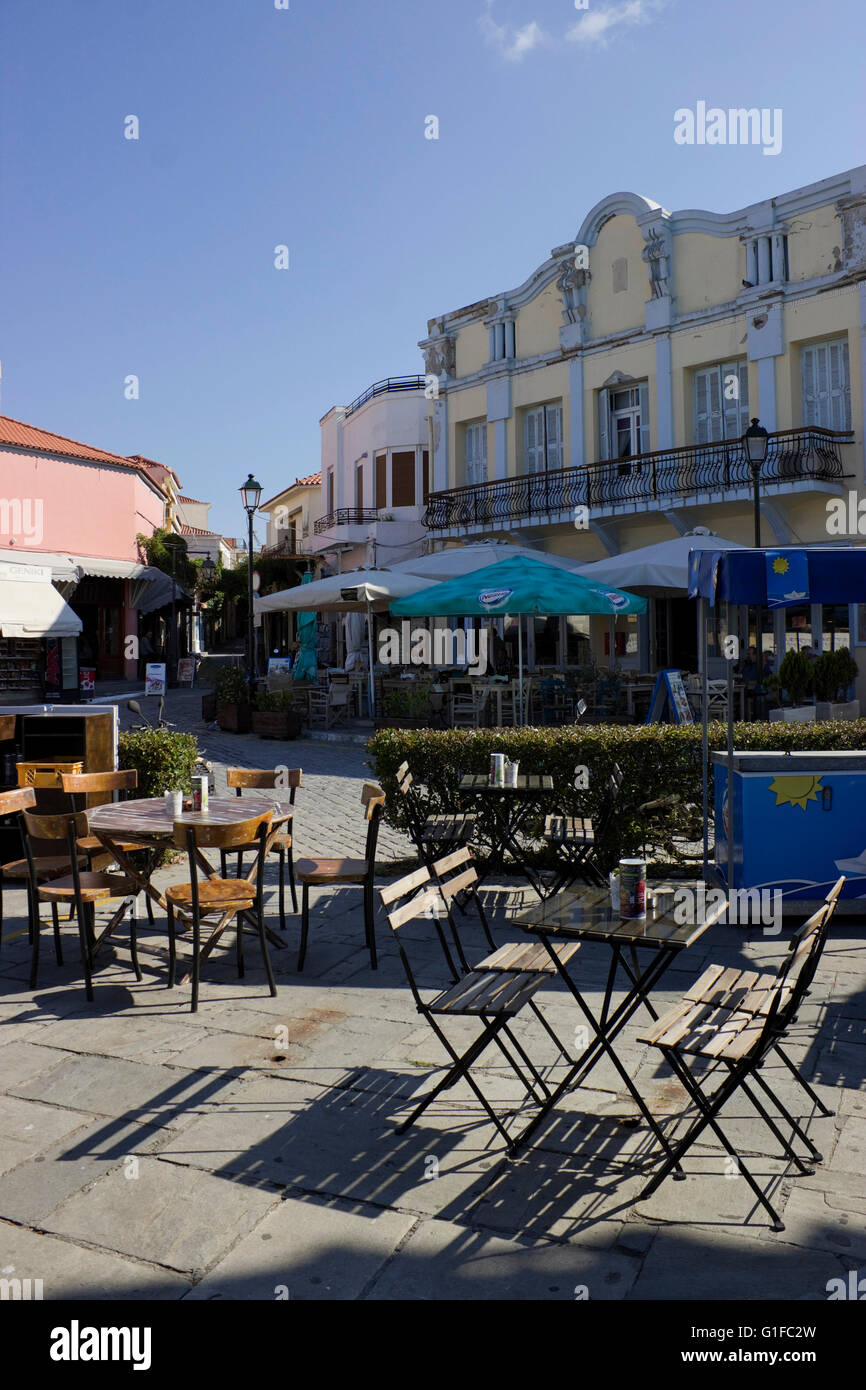 Cafee tables & seats on sidewalk of Myrina's promenade square and neoclassical buildings at the beginning - Stock Image