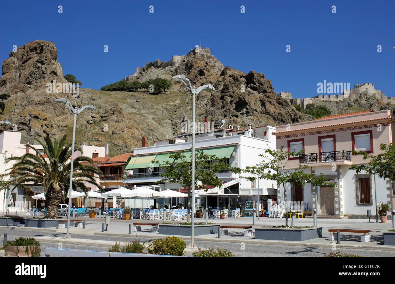Street cafee, restaurants and planted trees at the waterfront of Myrina and the castle in background. Limnos island, - Stock Image