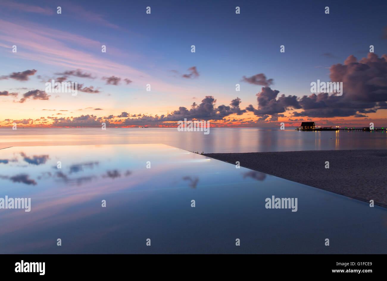 Infinity pool at Olhuveli Beach and Spa Resort at sunset, South Male Atoll, Kaafu Atoll, Maldives Stock Photo