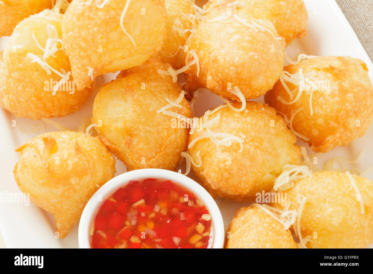 Cheddar cheese Beignets with chilli dipping sauce - Stock Image