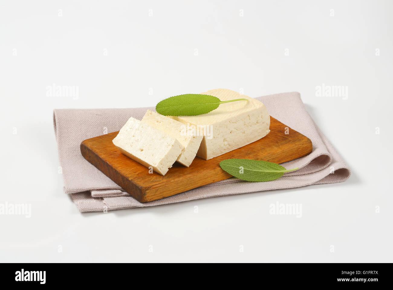 block of fresh tofu on cutting board - Stock Image