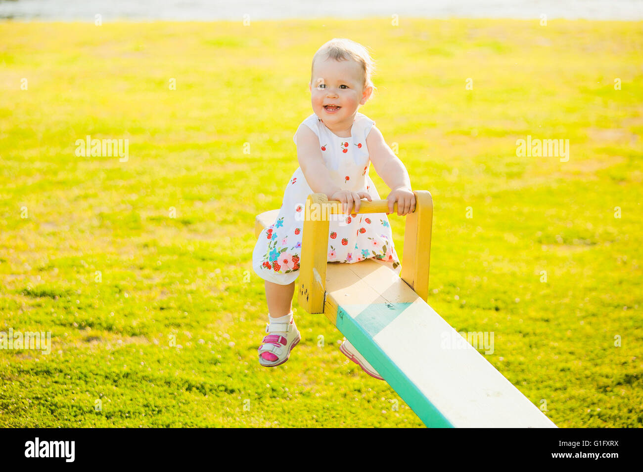 Little girl enjoying riding swing with mum at beautiful nature background. Baby happily playing with parents outside - Stock Image