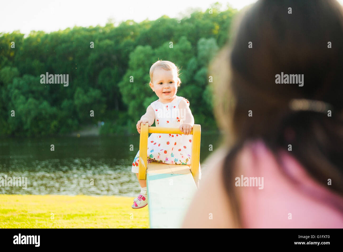 Little girl enjoying riding swing with mommy at beautiful nature background. Baby happily playing with parents outside - Stock Image