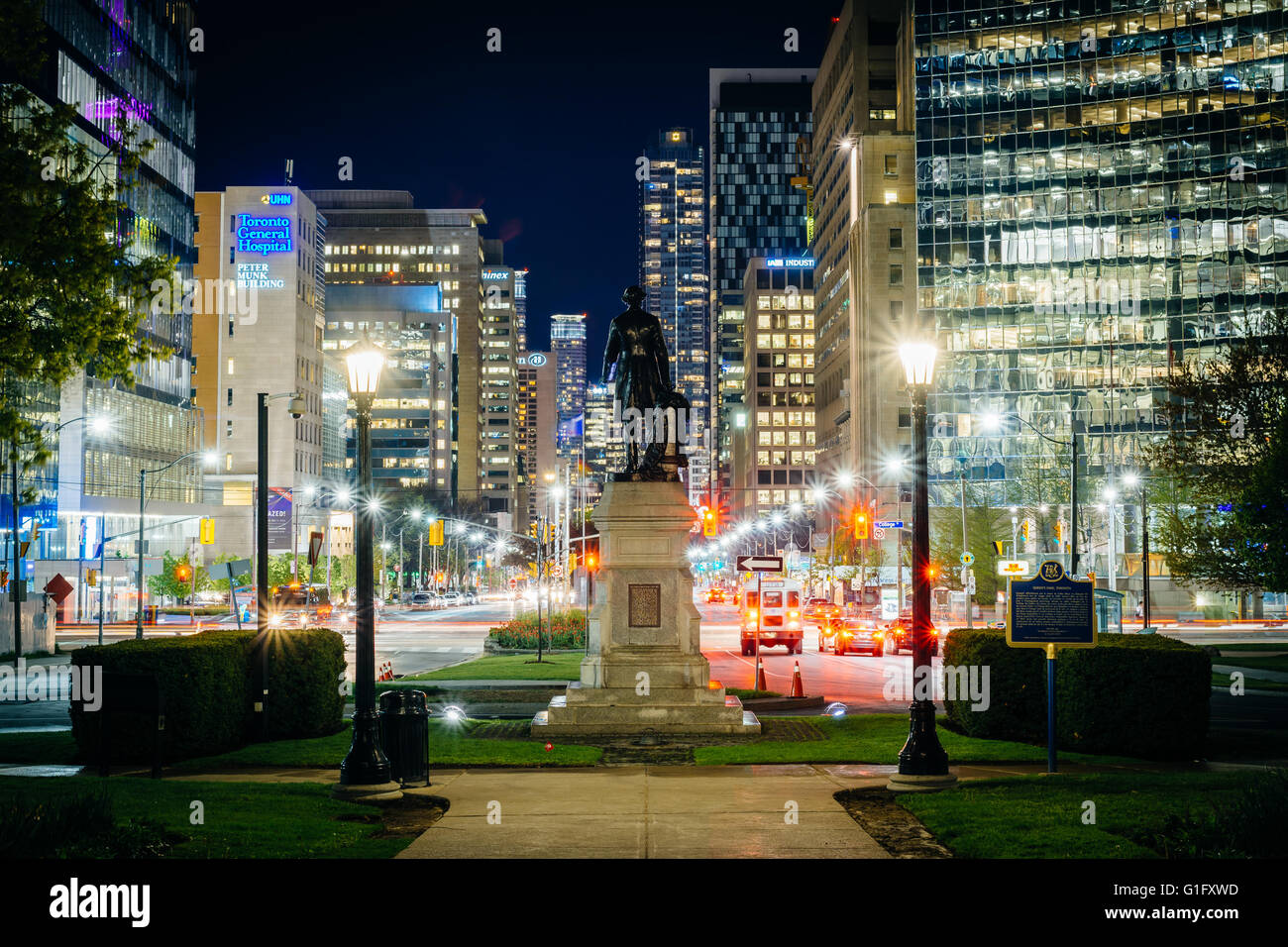 Statue and walkway at Queen's Park, and buildings on University Avenue at night, in Toronto, Ontario. - Stock Image