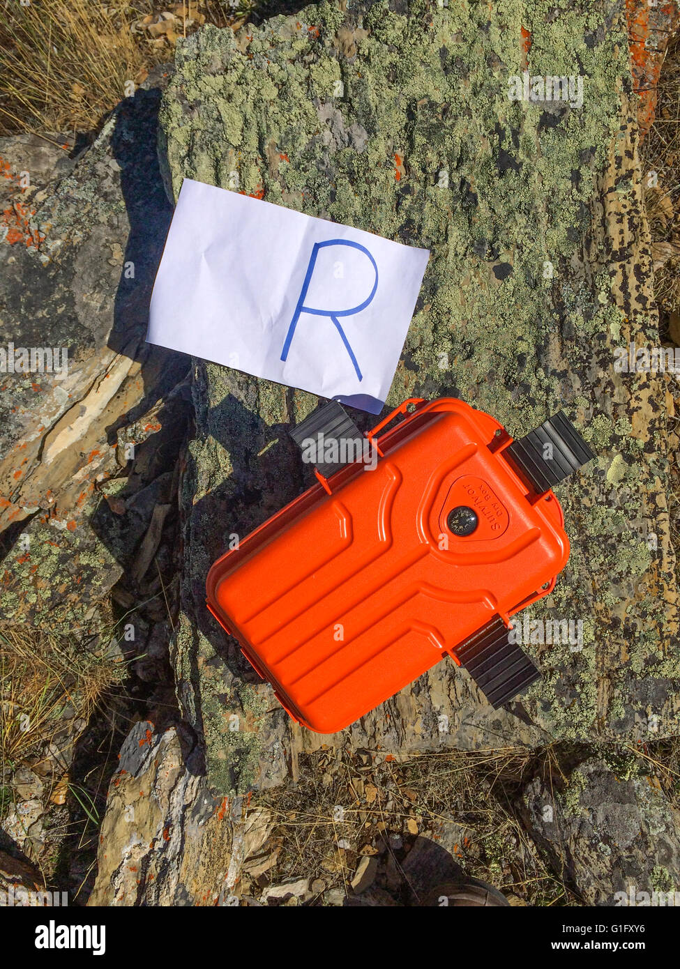 orange geo cache with a piece of paper with an R - Stock Image