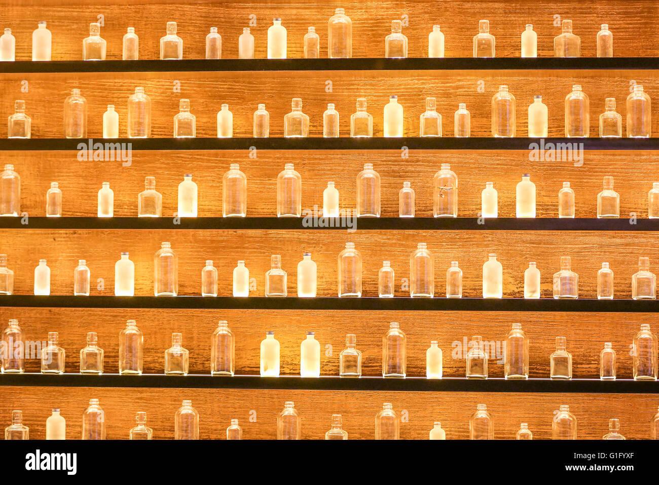 empty bottles of various sizes on shelves lite with light Stock Photo