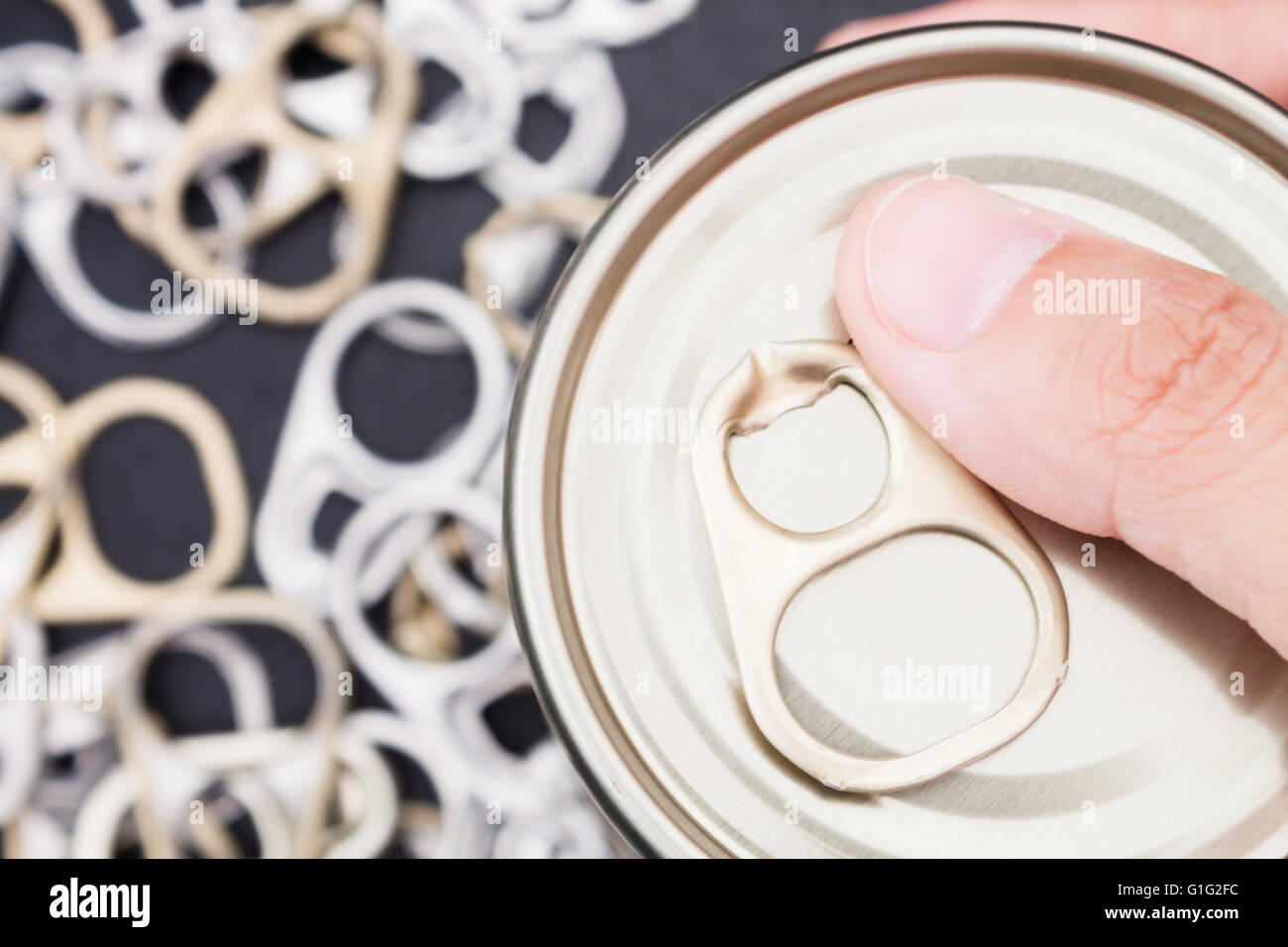 Woman hand holding ring pull cans opener on black metallic background - Stock Image