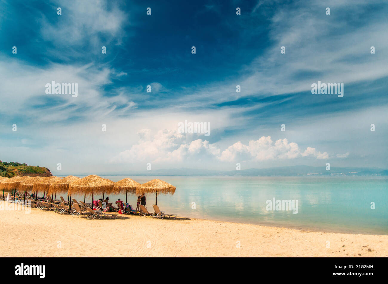 Thatch umbrella, sunbeds on a greek beach and clouds reflections in the turquoise waters of the Aegean Sea, Nea - Stock Image