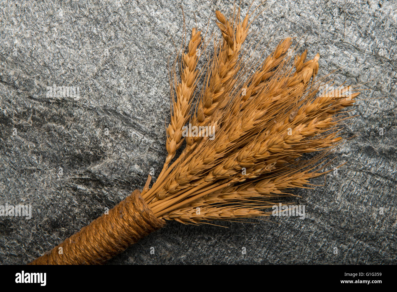 Dried wheat and straw on stone background - Stock Image