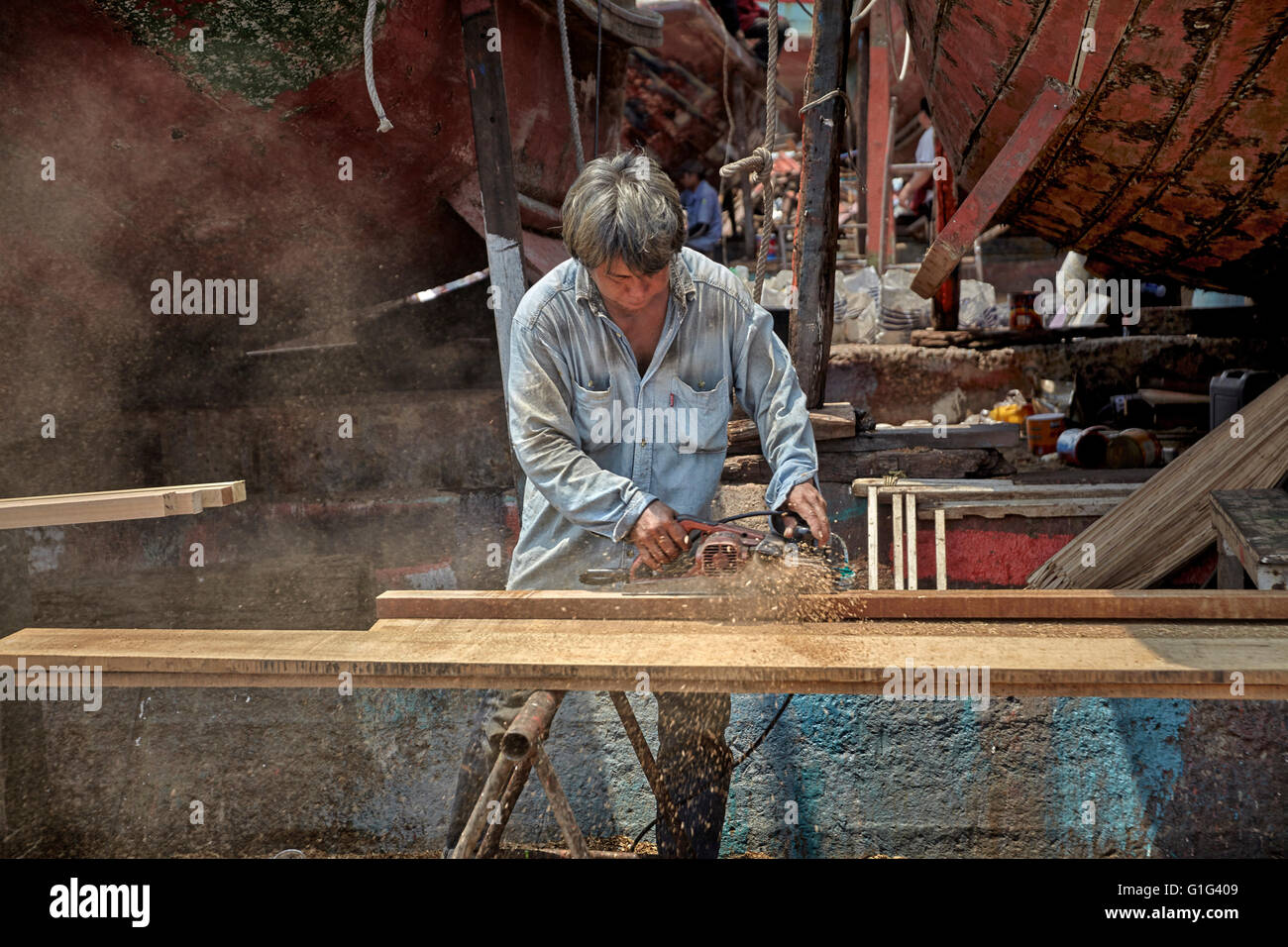 Carpenter working with wood using a power  tool. - Stock Image