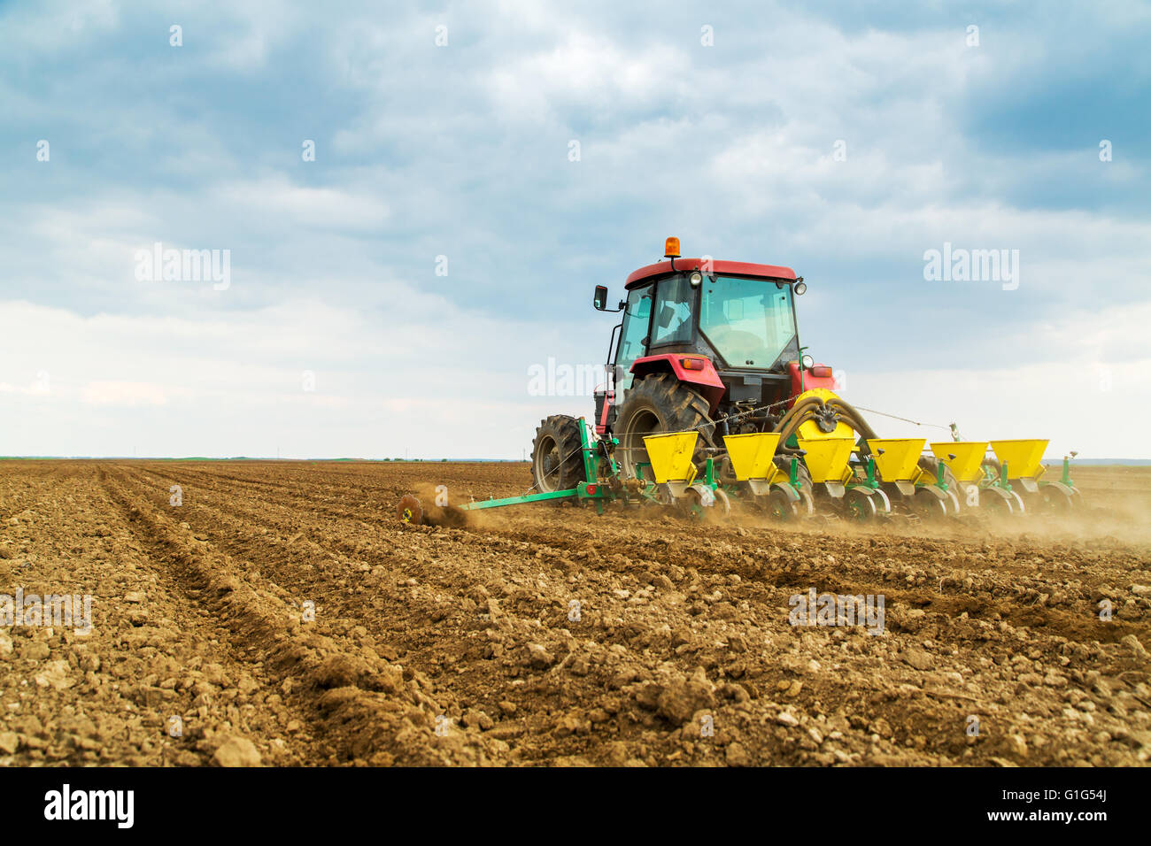 Farmer seeding crops at field - Stock Image