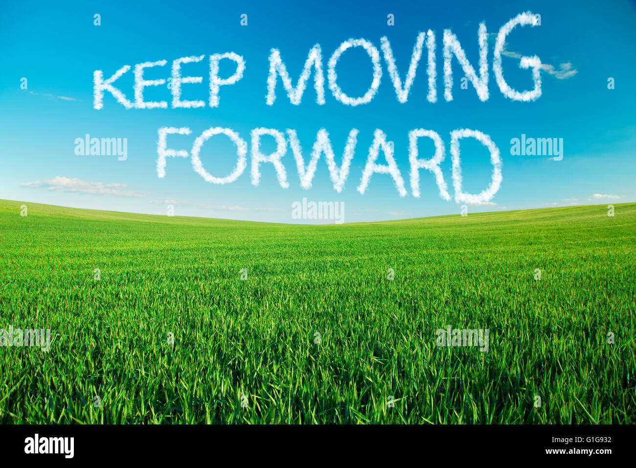 Keep moving forward written in clouds over green field - Stock Image