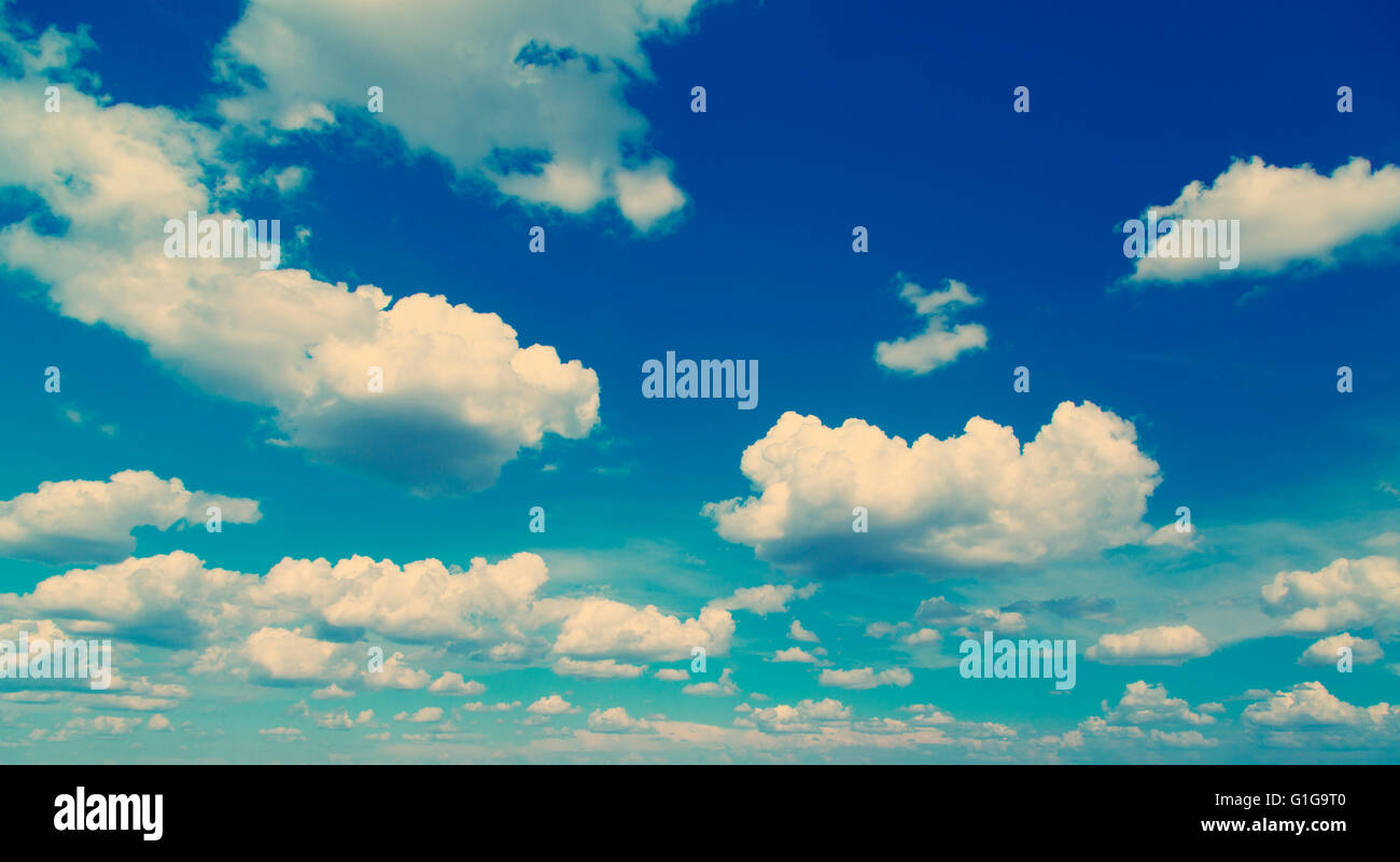 White fluffy clouds over blue sky, filtered instagram look. - Stock Image