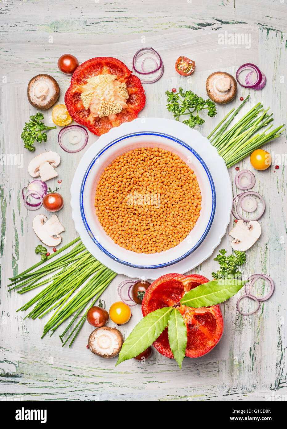 Red lentil in bowl and vegetables ingredients for healthy vegetarian cooking, top view composing. - Stock Image